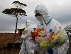 Tomoe Kimura (right), an evacuee of Okuma town, holds a bouquet with another evacuee as they walk towards a mourning event for those killed by the disaster during a temporary visit to the nuclear exclusion zone in Okuma town, Fukushima Prefecture on March 11, 2012. (Kim Kyung-Hoon/Reuters) // www.boston.com/bigpicture/2012/03/japan_remembers_rebuilds.html