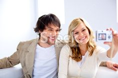Smiling couple laughing taking self portrait photo on a sofa Royalty Free Stock Photo With coupon codes and promotional codes.
