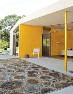 WOW...bright yellow accent walls & OMG I LOVE~LOVE THE PATIO FLOORING!! What a GENIUS idea to use sliced tree trunks & gravel...I'm sooo doing that!!!! <3