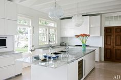 The kitchen in a Shelter Island, New York, home designed by Russell Piccione features Boffi cabinetry and Jeff Zimmerman pendant lights; the cooktop is by Viking, and the porcelain tableware is by Hermès. Architectural Digest, Kitchen Pendant Lighting, Kitchen Pendants, Pendant Lights, Beach Kitchens, Modern Farmhouse Kitchens, White Kitchens, Dream Kitchens, White Kitchen Cabinets