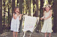 """A personalized banner can make for a delightful flower girl prop. Stuck on text? Consider the traditional """"Here comes the bride"""" or """"Please rise for the bride"""". For something a little less formal, a simple """"Yay!"""" or """"Oh Happy Day!"""" can express the perfect sentiment."""
