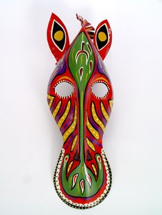"""Zebra Mask Wall Hanging. African masks should be seen as part of a ceremonial costume, and animals are common subjects in African masks. Animal masks connect people with the spirit world that traditional African beliefs say inhabit the forests and open savannas. An animal is also a symbol of specific virtues. The zebra represents beauty in individuality and integration of opposites. Height: 17"""" Width: 7.5"""" Artist: Mkankha Brothers Made In: Zimbabwe $58.00"""