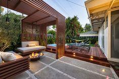 Área de descanso en patio seco, con pergola de madera y piso deck. Estilo minimalista