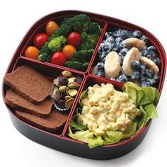 "This egg salad bento box is a hearty lunch and snack all in one. Spoon the egg salad into a lettuce ""bowl"" to keep it looking pretty and enjoy with cocktail bread and veggies. Toss banana and blueberries with yogurt to keep the bananas from turning brown. Save the chocolate chips and pistachios for an afternoon pick-me-up. @EatingWell"