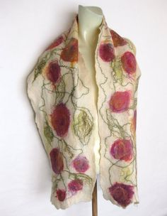 Hand felted scarf, in a Cobweb felt technique, made with off-white, soft Merino wool and embellished with Silk fiber. Cobweb felt is lightweight, warm, soft and lacy, holes are part of the work technique. Approximate measurements: 64 x 11 Care: hand wash in cool water, squeeze gently