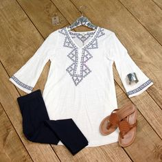 Wedgewood Tunic is sophisticated styling. This ivory tunic is lightweight with a navy aztec embroidery detail around the front and back bodice and sleeve trim.