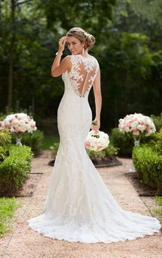 This vintage lace trumpet wedding dress by Stella York features lace and tulle over lavish satin that creates a sleek silhouette. A soft organza back plays into a substantial train with a scallop lace edge finish for a truly romantic walk down the aisle. The deep sweetheart neckline is accented by illusion lace straps that create a comfortable, yet glamorous neckline. A zipper closure is hidden under fabric-covered buttons. This beautifully vintage wedding dress is available in plus sizes.