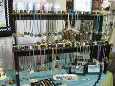 Interesting use of spools nailed onto wood strip, then painted, for necklace hangers. MUCH easier to get necklaces off than a single stick across is.