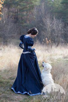 Auf der Suche nach Eleganz und Reiz? Dieses Kleid ist nur das Richtige für Sie! Aus Baumwolle gefertigt, mit einer schönen Borte und mit kleinen Knöpfen an Ärmeln verziert, wird es Ihr Mittelalter-Look perfekt vervollständigen.