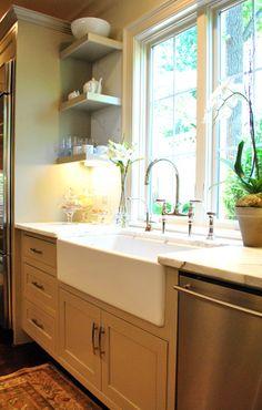 farmhouse sink, marble, floating shelves, apothecary jars w/ pretzels & etc, orchid