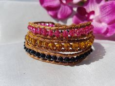 This is a fashionable handmade triple wrap bracelet. Its made with leather cord and three different colour glass beads. Its fastened with an acrylic bead  Length 21.75 inches (56 cm) To fit wrist 7 inches (18 cm)