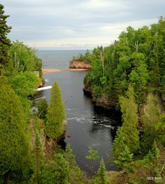 Baptism River into Lake Superior, Tettegouche State Park, Minnesota, USA. Tettegouche State Park - the spectacular overlooks at Shovel Point; rocky, steep cliffs and inland bluffs; the cascading 60 ft. High Falls of the Baptism River; and the historic Tettegouche Camp where visitors can stay the night. This is a hiker's paradise with miles of trails that overlook the Sawtooth Mountains and wind down to inland lakes accessible only by foot.