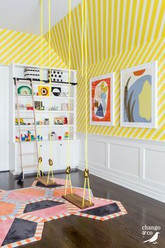 Two neon yellow swings with wooden seats hang in a playroom over multi-colored hex carpet tiles and in front of a white wainscot wall lined with yellow diagonal striped wallpaper. Source by decorpad ideas for teens Modern Playroom, Playroom Design, Kids Room Design, Yellow Playroom, Modern Kids Bedroom, Modern Kids Decor, Colorful Playroom, Bedroom Wall Ideas For Teens, Bright Bedroom Ideas