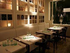 White on white - Wall of shelving - white mullion doors sans the glass. La Crema Canela Restaurant Barcelona, Spain.