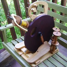 Cute little spinning wheel. Purple wheel, and foot-shaped treadles!