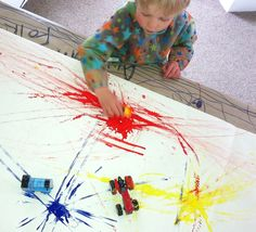 Painting with cars.  Talking about colour theory - primary colours (red, blue & yellow) mixing to make secondary ones (red & blue = purple, red & yellow = orange, yellow & blue = green.)