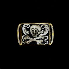 Pierced gold mourning slide, with enamelled skulls, crossbones, a winged heart, flowers and leaves, England, mid 17th century.