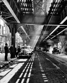 The Bowery in the shadow of the Third Avenue Elevated. New York, 1940.  by Andreas Feininger