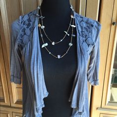 Grey top with lace detail This top would be worn over perhaps a Cami, or other shirt.  It's a beautiful dove gray with lace detail on the shoulders and across the back. The front and back draping is very sweet and lends for a terrific look! Tops