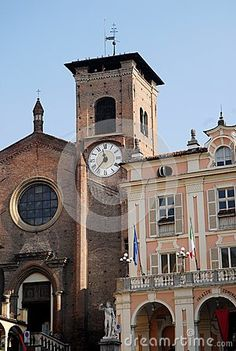 Photo made in Moncalieri near Turin in Piedmont (Italy). In the image you can see the façades of a church, probably the cathedral, and the building that houses the Town Hall. In front of the church stands the large rose window and the bell tower with the clock in the Town Hall the statue to the left, the large porch, the long balcony and large windows.