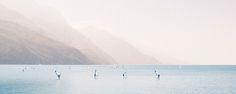 Windsurf – Gardasee-Panorama mit Surfern. Der Dunst der Szene lässt die ins Wasser ragenden Berghänge wie eine Entfernungstabelle ins Nichts laufen. 2014, PP | © www.piqt.de | #PIQT