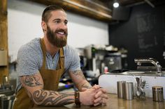 Smiling hipster barista at coffee shop counter. Sams boss Hugo has a knack for building streamlined coffee shops and emptying the trust fund account . Hipster Coffee, Hipster Man, Chefs, Coffee Shop Counter, Coffee Shops, Shop Plans, Dinners For Kids, Confectionery, Online Shopping Clothes