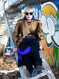 Accidental Icon wears a silk wrap top, skirt, tights, lug-sole boots, statement earrings, and round sunglasses