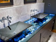 Love the blue light and stones under glass. Only need one sink tho