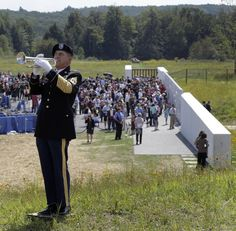Sgt. Robert Baranik plays Taps following a ceremony to commemmorate the 10th anniversary of the Sept. 11, 2001 terrorist attacks, on a hill above phase 1 of the permanent Flight 93 National Memorial near the crash site of Flight 93 in Shanksville, Pa. Sunday Sept. 11, 2011. The crash site of United Flight 93 is marked by the large rock in the distance. (AP Photo/Amy Sancetta)