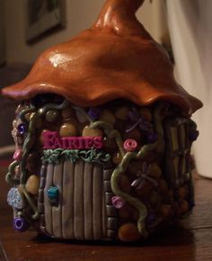 fairy house made by using a jar and covering in clay, then hand setting each stone and using small buttons... fimo sculpey polymer clay by Rosie McPherson