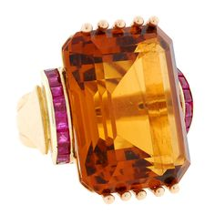 The large center stone is an emerald cut citrine, which rests in a 10 prong setting. Description from 1stdibs.com. I searched for this on bing.com/images