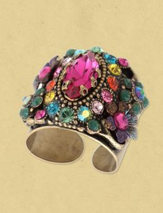 Michal Negrin cuff ring with a marquesas stone , multicolor sparkling Swarovski crystals, matte turquoise beads and painted flowers. Adjustable band. Measures 1 1/4 inch high. Nickel-free brass.