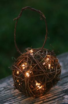 """6"""" round grapevine balls with 4"""" handles that has been filed with moss and battery operated string of lights"""