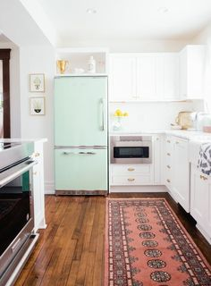"White kitchen with mint fridge // After a year-long renovation, Diana moved into this ""collected eclectic"" style Ann Arbor house."