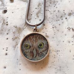 Owl necklace made from one of my Owl drawings. This necklace was made from a copy of my drawing and sealed inside this sterling silver shadowbox with resin. It has a brass guitar nut on top where the jump ring is attached. I stamped a tiny heart and a little wing on the back. This necklace