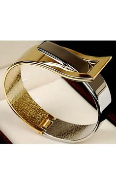 The bangle crafted in alloy, featuring chic but simple design with glossy appearance, contrast color detail and inset fastening. Chic design with unique personality.