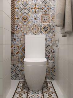 Орнаменты кафельной плитки в туалете образуют ковер на полу и стене.