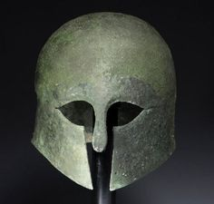 Corinthian helmet, 6th-5th century B.C. A fine bronze Corinthian helmet formed of one sheet of bronze, with traditional eye openings, nose guard, and subtle short rear flange, 21,5 cm high. Private collection, from Artemis gallery