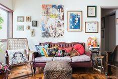 Sofá vintage de couro, almofadas coloridas, parede galeria e muitas peças garimpadas.
