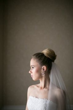A bun on the big day with clip-in veil in the back only