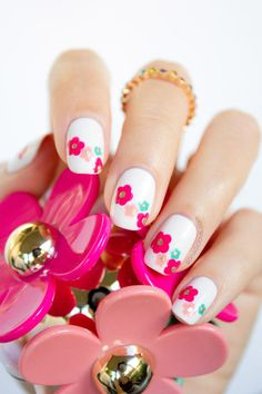 As if we weren't in love enough with Marc Jacobs' Daisy Delight fragrances, this adorable nail look came along and swept us off our feet. And it's so easy if you already have the colors in your collection! Paint all your nails with an opaque white base coat. Then dot on five-petaled flowers in fuschia, pale pink, and teal. Pay attention to the way the flower sizes vary. We recommend using a dotting tool to keep petal sizes consistent. Finally, add a shimmery gold center, and finish with a…