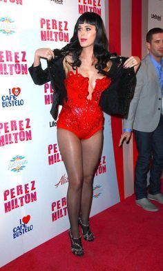 Katy Perry in a red corset, black hose, and heels