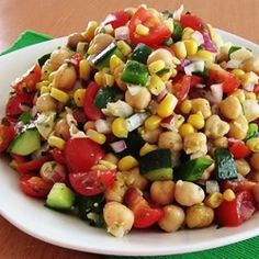 Cold salad made with corn, chickpeas, cucumber, cherry tomatoes, green pepper and red onion with a cilantro-lime vinaigrette.