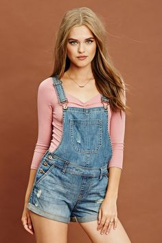A pair of denim overall shorts featuring a distressed front, a five-pocket construction, burnished snap buttons, and adjustable straps.