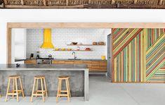 Concrete island, subway tile backsplash, vivid wood slats.
