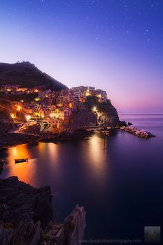 Celestial Coast - Manarola, Cinque Terre, Italy. The night sky slowly fades away over Manarola, a picture-perfect fishing town perched on the cliffs of the Mediterranean Sea. Each day, way before sunrise, this jewel on the Italian coast awakes from its nightly sleep, as fishermen return from the sea and the scent of freshly brewed coffee starts to fill the still empty streets. I can't think of a more perfect way to start the day.