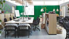 会議用テーブル(バーチ材突き板、脚はシルバーカラー)、オープンシェルフユニット、扉付きシェルフユニットを設置した開放的なオフィス