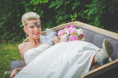 Bride on a couch outside in woods.