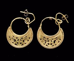 A PAIR OF BYZANTINE GOLD EARRINGS CIRCA 7TH CENTURY A.D. Crescentic in form, with an openwork design consisting of two stylized facing peacocks on either side of a central encircled quatrefoil, the details incised, a deep drill punch for the eyes, the crescentic elements framed below by a beaded wire, the thin hoop along the concave edge, re-soldered in place in modern times; now joined to modern gold ear wires