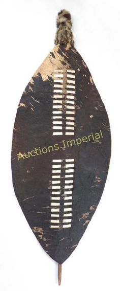 A RARE ZULU ISHILUNGA SHIELD A large example, the type developed by King Shaka kaSenzangakhona, popularly known as Shaka Zulu, in the early 19th century. Formed of a single section of cowhide with the hair intact, primarily black with a small area of white, and interwoven with white hide strips to strengthen it; the reverse with a hide grip and well-scraped pole capped with a tassel composed of spotted fur sections. Late 18th- early 20th century. Overall length 150.5cm.